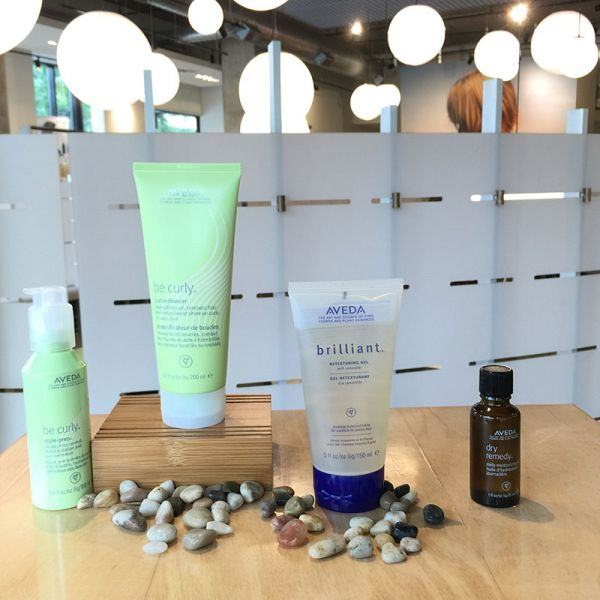 Display of Aveda beauty products and pebbles on a table