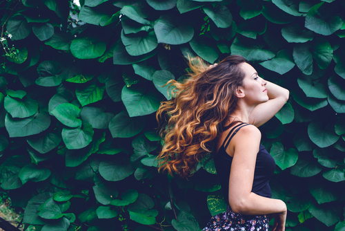 Aveda model with hair in the wind in front of a wall of ivy leaves