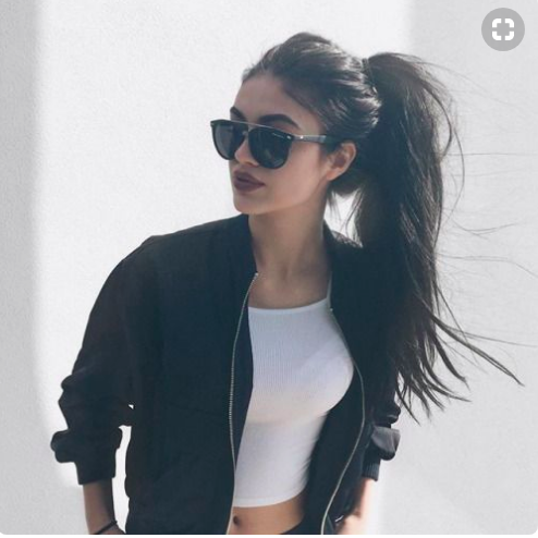 Beautiful girl with long brown ponytail wearing sunglasses.