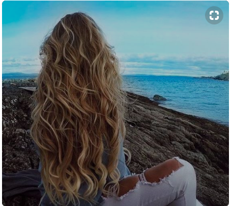 Girl with long, blonde waves sitting by the oceans.