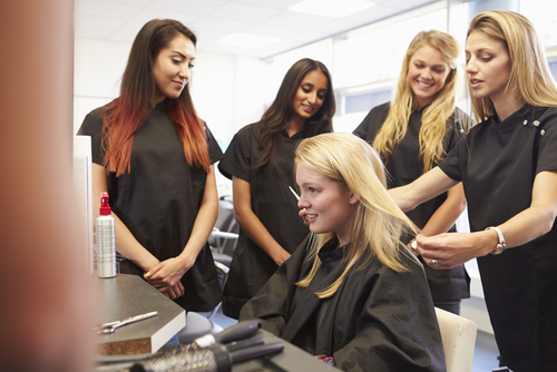 multiple women style a blonde woman's hair in a salon