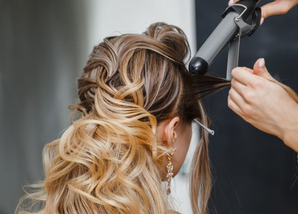 woman getting her hair styled with curling iron