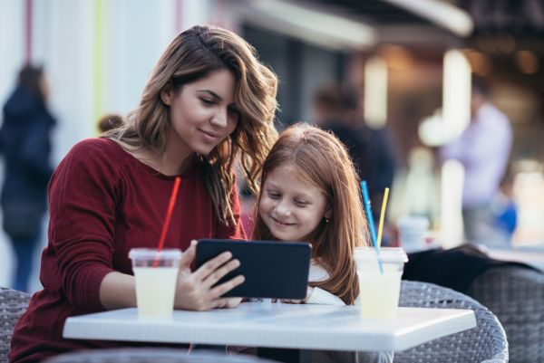 mother and daughter at a cafe look at tablet together